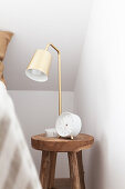 Lamp and alarm clock on solid wooden stool used as bedside table