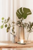 Eucalyptus, olive and Swiss cheese plant leaves in vase