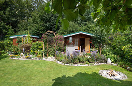 Summer garden with sheds, lawn, flower beds, and firepit