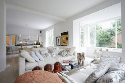 White sofas with scatter cushions next to window in open-plan interior