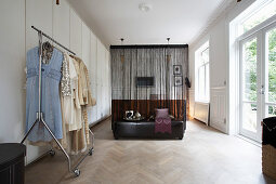 Lady's clothes on clothes rail; bed in background behind translucent curtain