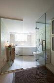 Corner bathtub in bathroom behind glass wall