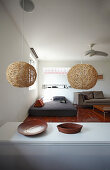 Pendant lamps above kitchen counter and view into living area with teak floor