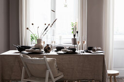 Table set with linen tablecloth and black crockery