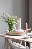 Spring bouquet with tulips and pastel pink candle on table