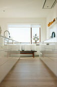 Kitchen with white, high-gloss cabinets and view of bench with cushions