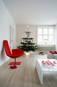 Red designer chair, tealight holders on white coffee table and Christmas tree in living room