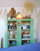 Antique glass-fronted cupboard painted green