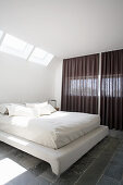 Double bed with white bed linen in bedroom with skylight