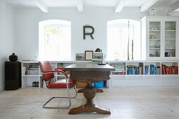 Solid wooden desk, red chair and white shelves in study