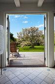 View through open door into sunny wooden terrace