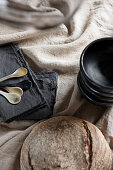 Black dishes, black napkins and bread on a beige linen tablecloth