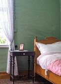 A wooden bed and a bedside table against a green wall in a bedroom