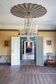 A room with wooden floorboards, a chandelier and portrait paintings