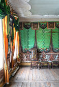 Antique chairs in a room with wooden floorboards and green wallpaper
