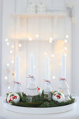 A tray with four white candles, Christmas baubles and fir sprigs