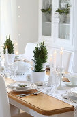 A table laid in white for Christmas dinner decorated with small trees