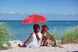 Mädchen mit Sonnenschirm und Hund am Strand