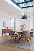 A round dining table with grey chairs and a vintage chest of drawers in a loft apartment with a skylight
