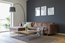 A brown leather couch, an arc lamp and a coffee table in front of a dark wall