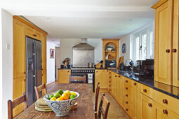 Fitted kitchen with wooden fronts and long table
