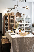 Set table with sand-colored tablecloth in front of showcases