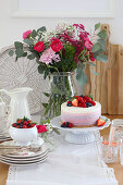 Berry cake and summer bouquet on table
