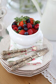 Summer berries and silver fork on stack of plates