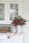 Jug vase with a bouquet of roses on the sideboard