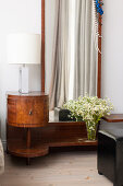 Antique bedside table with lamp and mirror in the bedroom