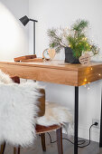 Small desk with Christmas decorations and chair with fur blanket