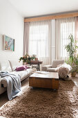 Bright upholstered sofa and rollable coffee table on a deep pile carpet in the living room