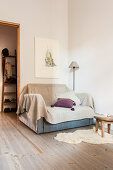 Sofa with throw and scatter cushions next to a floor lamp in the corner of a room
