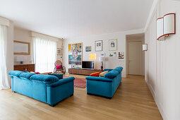 Blue upholstered sofas, TV furniture and rocking chair in the living room