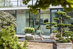 woman sitting on a terrace with an iPad,modern architecture in Hamburg,north Germany,Germany