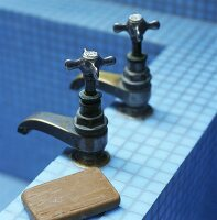 Two antique taps and bar of soap on edge of a blue tiled bathtub