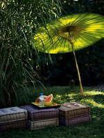 Slices of melon on cushions in open air, with green sunshade