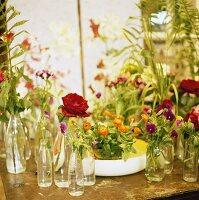 Verschiedene Blumen in Glasflaschen