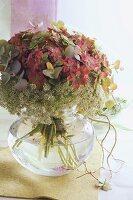 Flower arrangement with hydrangeas in glass vase