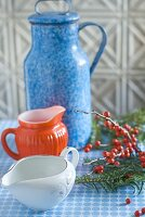 One large and two small jugs with red berries