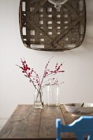 Woven basket on wall above twigs in glass jar on rustic wooden table