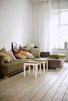Sofa mit Kissen im Altbau-Wohnzimmer mit Dielenboden