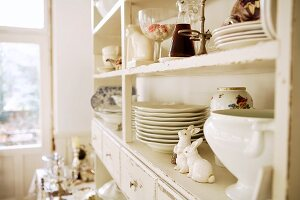 Crockery and ornaments on antique, white-painted kitchen dresser