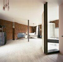 Schlafecke im Loft mit weissem Dielenboden und Ziegelwänden; mit Glasbausteinen abgetrenntes Bad ensuite