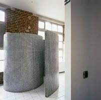 Geflieste Wand in Schneckenform als WC-Abtrennung in offenem Loft-Bad