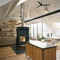 Offener Wohn/Essraum im ausgebauten Dach mit freistehendem Schwedenofen und Glasfront zur Dachterrasse