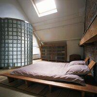 Dachloft mit Futon-Doppelbett und Bad ensuite hinter gebogener Wand aus Glasbausteinen