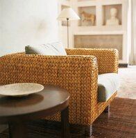 Moderner Sessel aus geflochtenem Schilfrohr neben rundem Beistelltisch