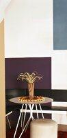 Kleiner, runder Tisch mit Eckbank und Polsterhocker vor grafisch bemalter Wand