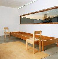 Zwei schlichte, moderne Holzstühle und ein langgestrecktes Holzgestell unter einem Fensterband
